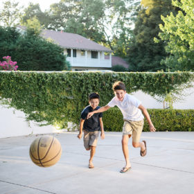 Brothers chasing after basketball in Sacramento backyard with fence growing ivy in background