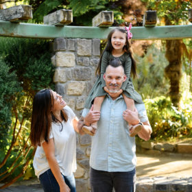 Mom laughing while dad carries daughter on shoulders in Land Park gazebo in Sacramento