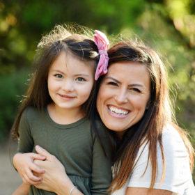 Mom smiling as she hugs daughter in Land Park Sacramento