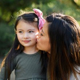 Mom kissing daughter's cheek in Land Park Sacramento