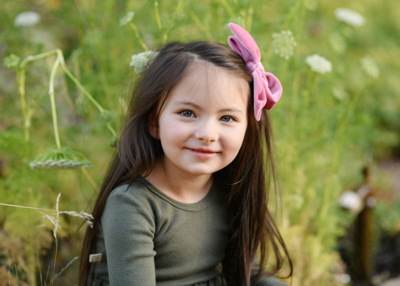Close up picture of daughter sitting in the grass at Land Park Sacramento