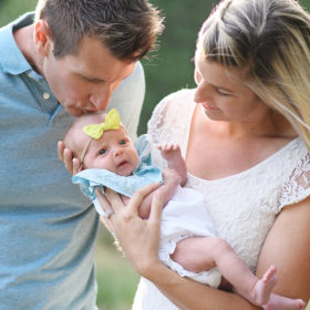 Dad kisses newborn baby daughter's head while mom holds her in natural light in Rocklin