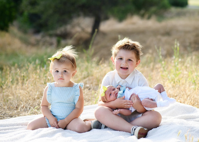 Toddler sister and big brother holding newborn baby sister on blanket on dry grass in Rocklin