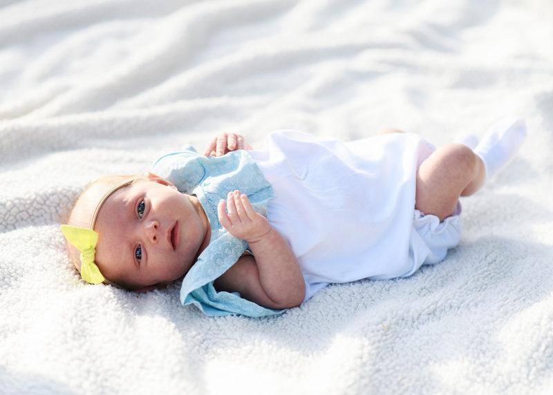 Newborn baby girl wearing yellow bow lying on white blanket in Rocklin park