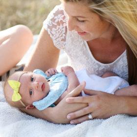 Mom holding newborn baby girl on white blanket in Rocklin park