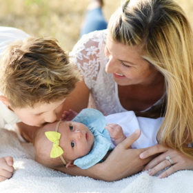 Big brother kissing newborn baby sister while mom watches on blanket in Rocklin park
