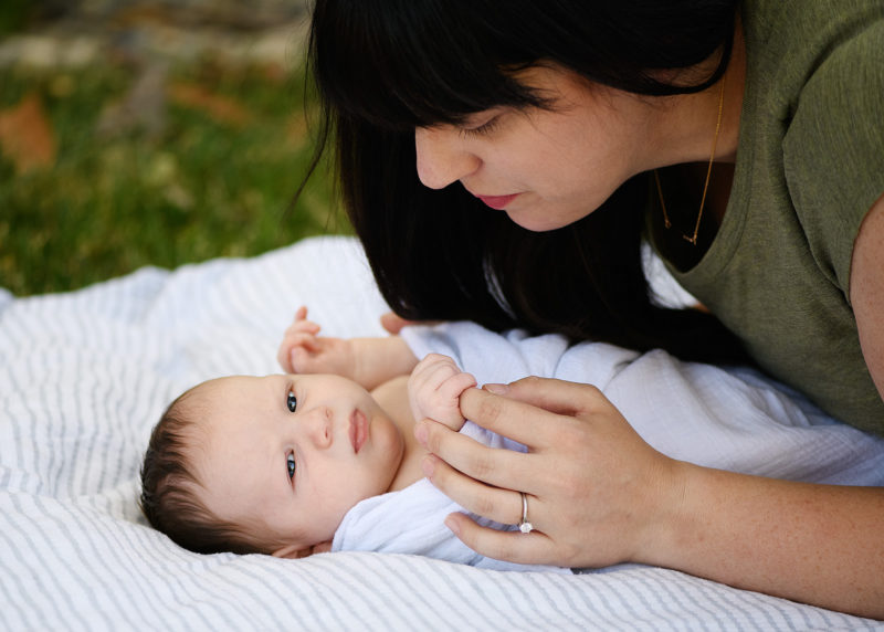 Mom holds newborn baby boy's hands on blanket in Sacramento backyard outside