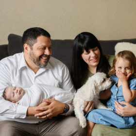 Big sister laughing while mom and dad smile at her while holding newborn baby in Sacramento home