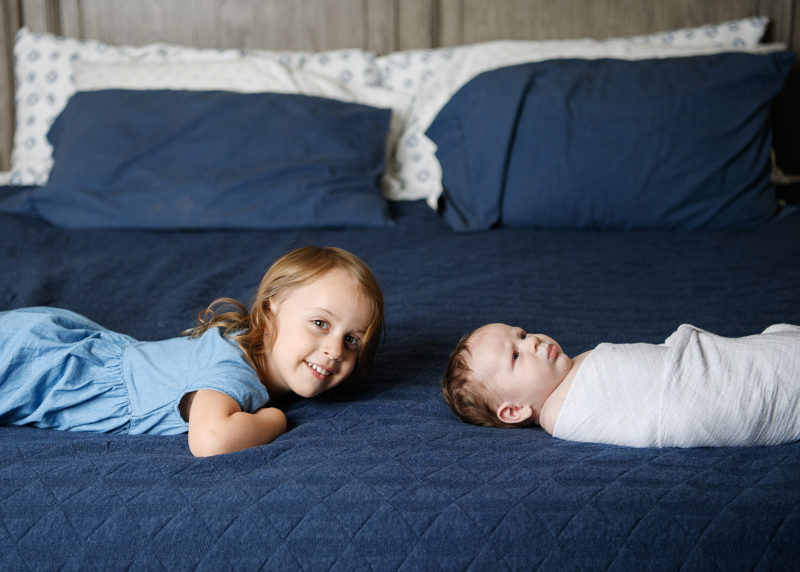 Big sister poses on blue bed with newborn baby brother in Sacramento home