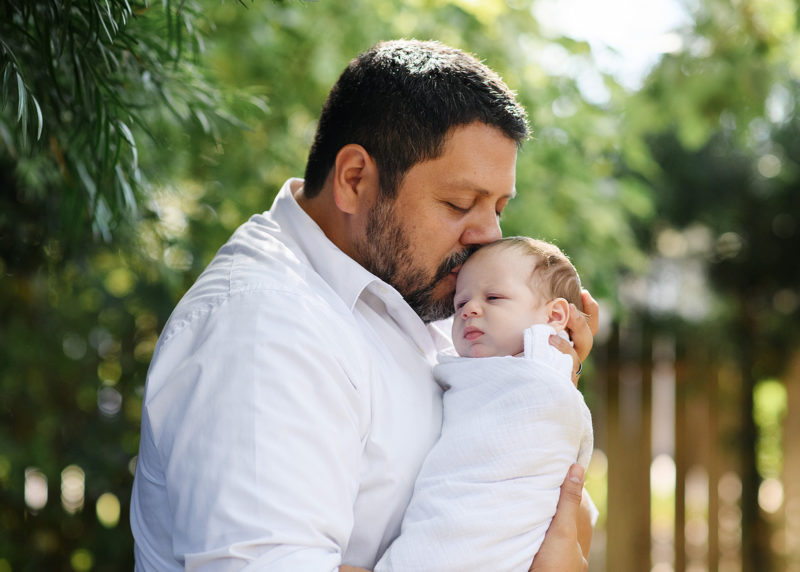 Dad kisses newborn baby on forehead outside in backyard natural light in Sacramento
