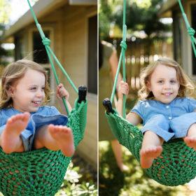 Toddler girl swings outside in Sacramento home backyard