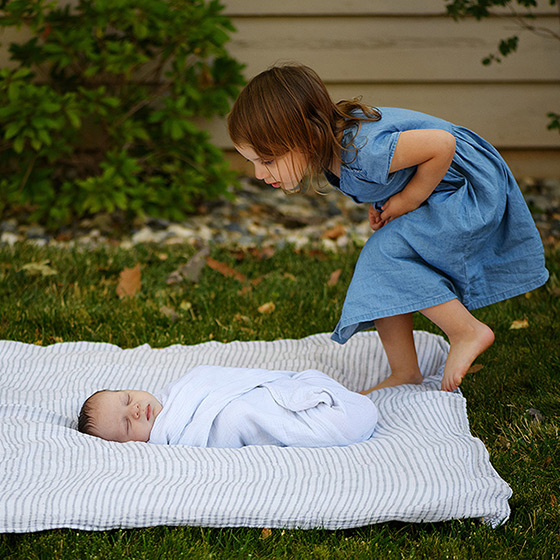 Big sister tip-toeing to check on newborn baby brother on blanket outside Sacramento yard
