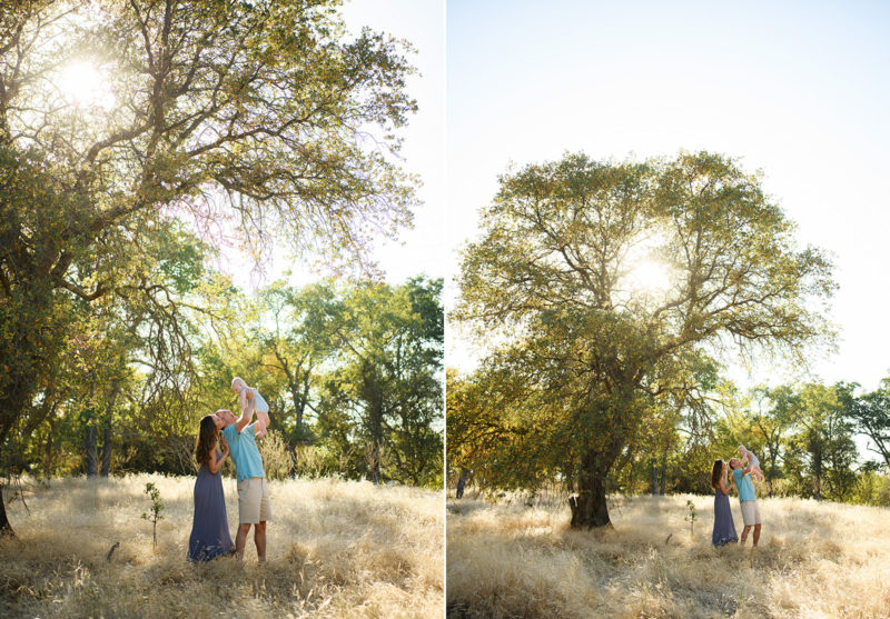 Wide shot of dad and mom holding baby boy while under a large tree in dry grass field in Davis
