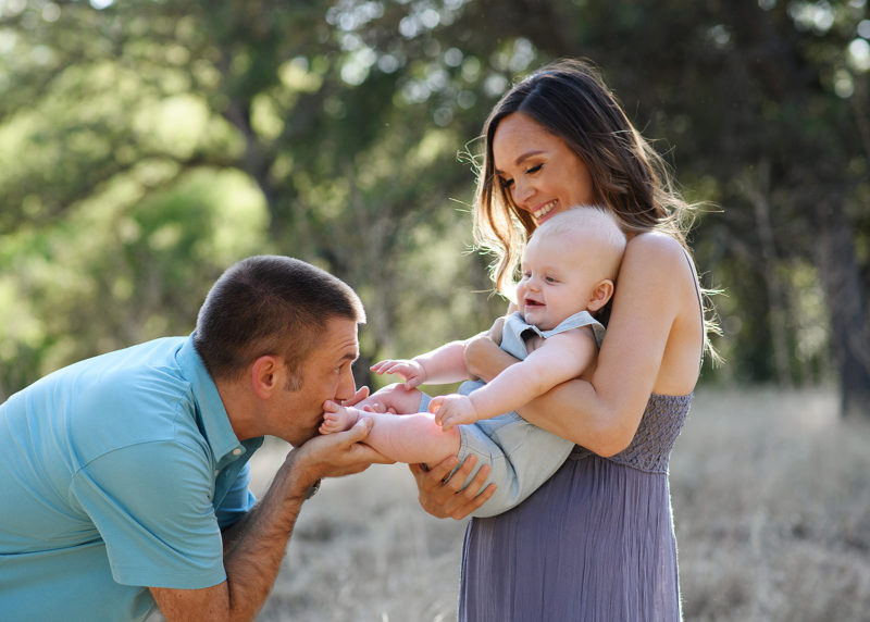 Dad kissing baby boy's feet while mom holds him with trees and dry grass in background Roseville