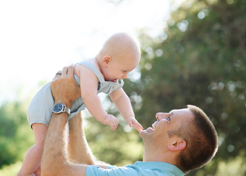 Dad lifting up baby boy in the air and smiling with trees and sky in background in Roseville