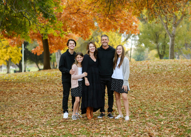 Family surrounded by fall foliage trees in Sacramento