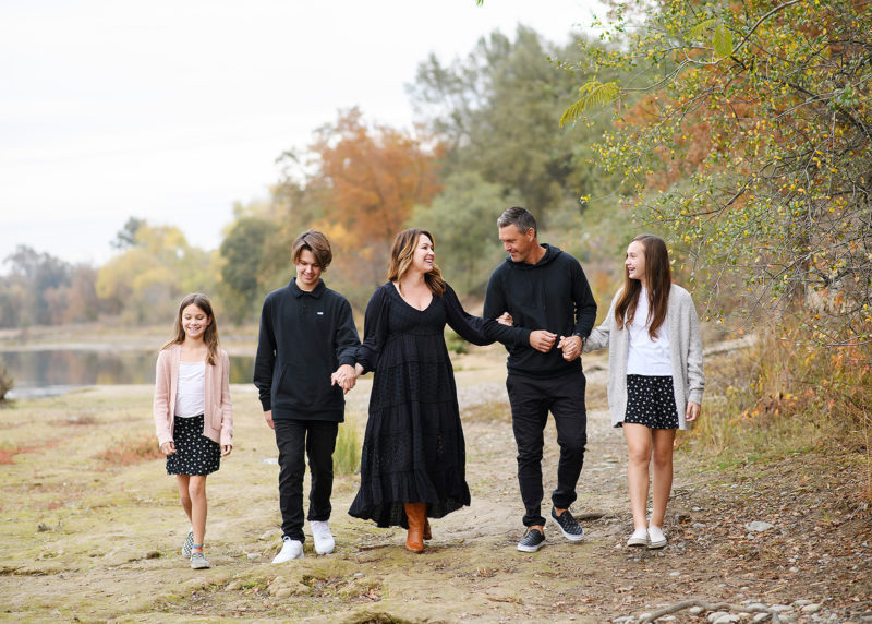 Family holding hands and walking by lake shore with trees changing color in background Sacramento