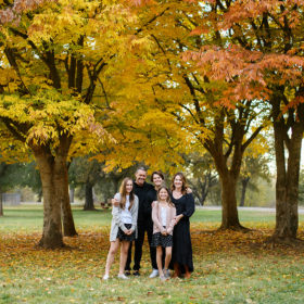 Family smiles for the camera underneath the canopy of fall foliage in Sacramento