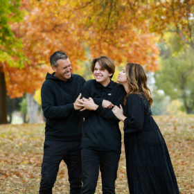 Lots of laughs as mom and dad hug son wearing all black with fall foliage background Sacramento