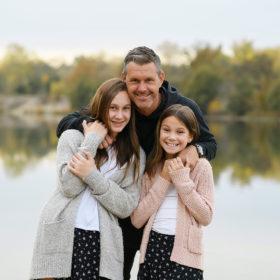 Dad hugging daughters by lake in Sacramento
