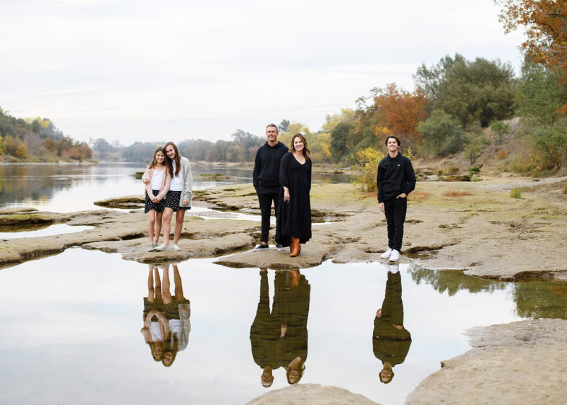 Family standing on rocks by the water with reflection on lake Sacramento