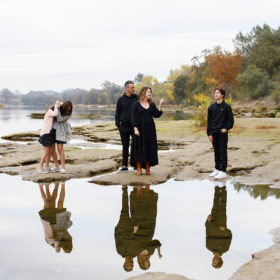 Family standing on rocks by the water being funny with reflection on lake Sacramento