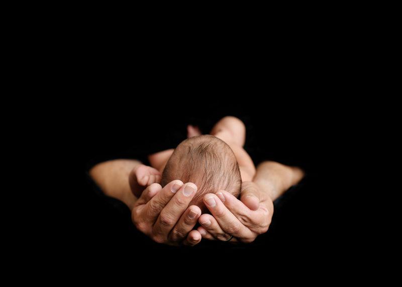 Newborn baby head close up being held by hands on dark black background in Sacramento studio