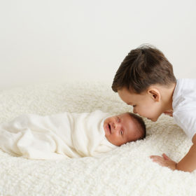 Big brother kissing newborn baby sister's head as she smiles on white blanket in Sacramento studio session
