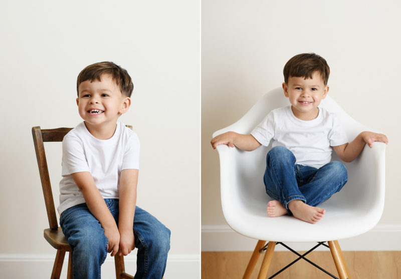 Toddler boy smiling and sitting on mid-century modern white chair and crossing legs in Sacramento studio