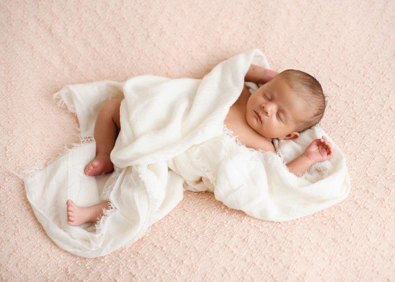 Newborn baby girl sleeping in white muslin swaddle on pink sheet in Sacramento studio
