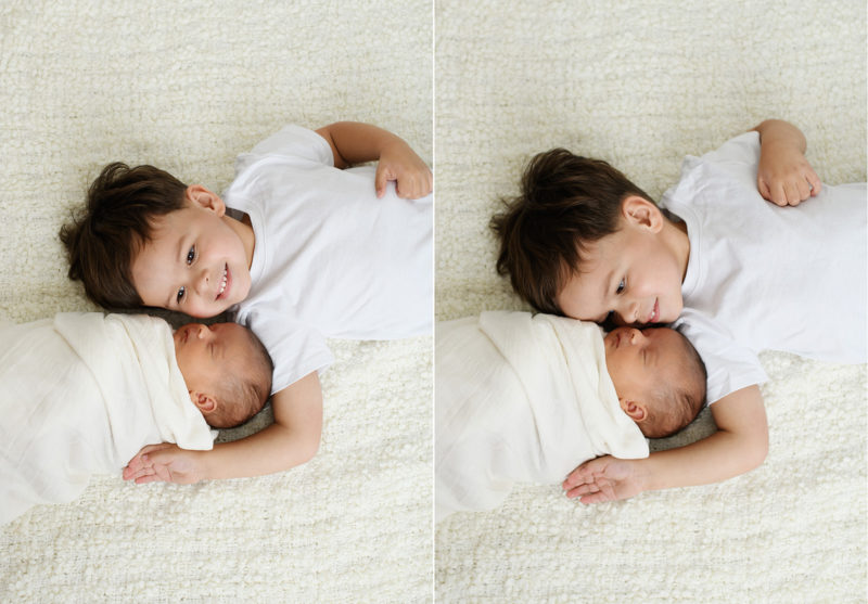 Big brother lying next to newborn baby sister on white blanket in Sacramento studio