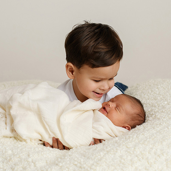 Big brother smiling at newborn baby sister in white swaddle and fuzzy blanket in Sacramento studio