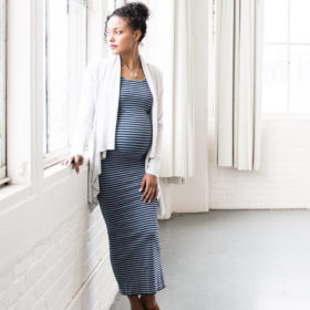Pregnant woman leaning on window sill wearing Moms The Word blue maxi dress
