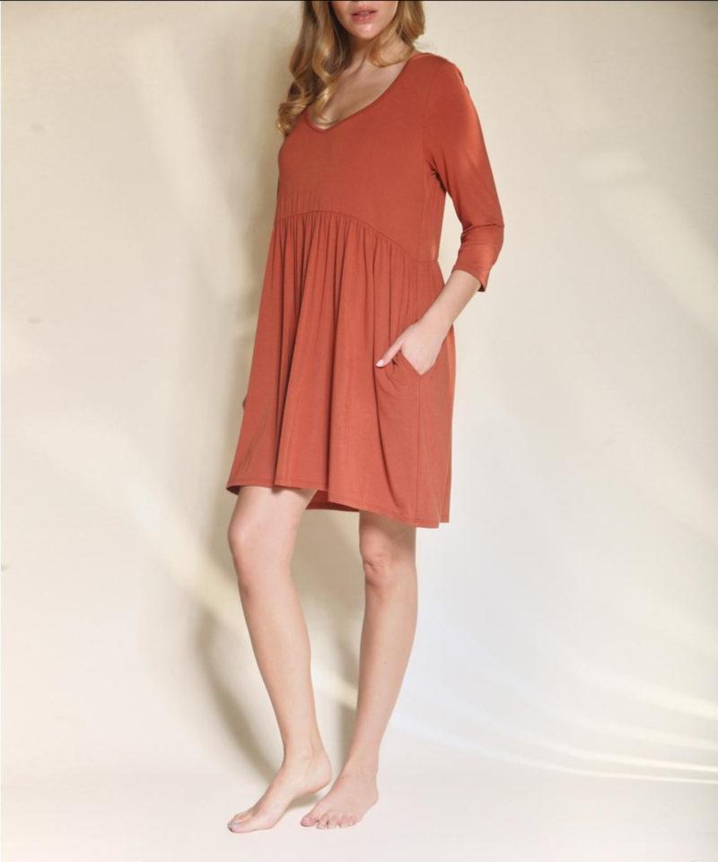Woman wearing rust colored Purpose Babydoll Bamboo Dress