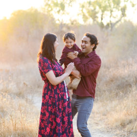Mom and dad hold son and smile at each other during sunset in Folsom