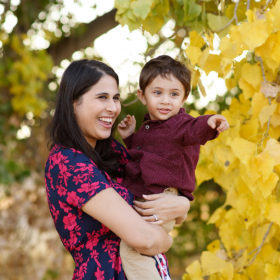 Mom holding son as he points with yellow leaves on trees framing the picture Folsom