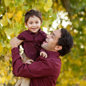 Dad smiling and holding son with yellow leaves on trees as background Folsom