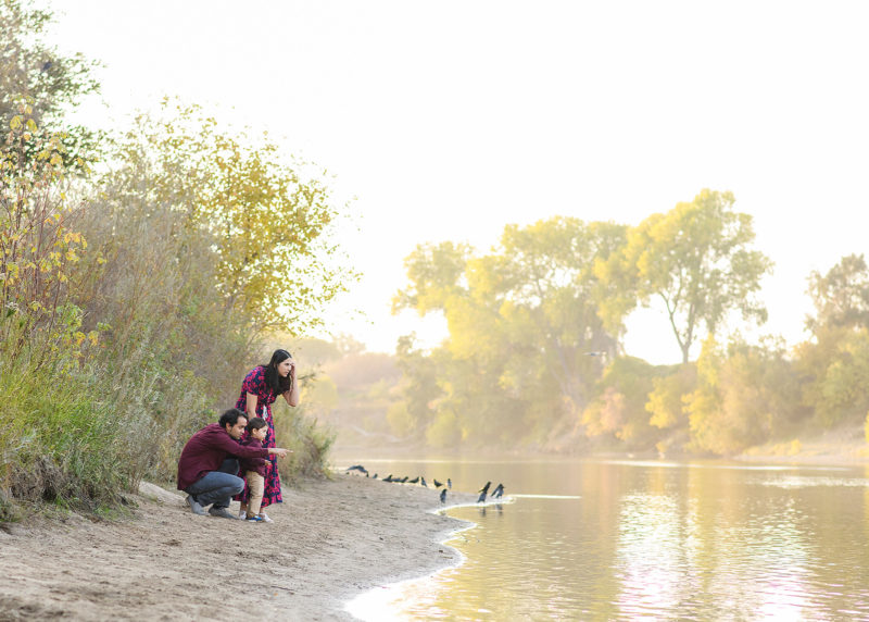 Family crouched down on the sand by the lake during sunset in Folsom