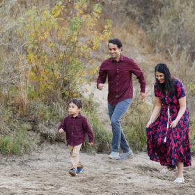 Little boy running in the sand as mom and dad run after in Folsom