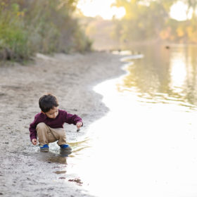 Little boy playing with stick in the lake in Folsom