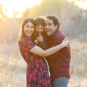 Family hugging with big smiles in golden hour light in Folsom