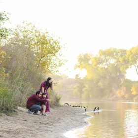 Family crouched down on the sand by the lake during sunset in River Park