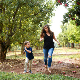 Mom running in apple orchard with son with apples on ground in Apple Hill