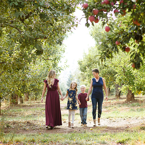 Moms walking with daughter and son in between apple orchards in Apple Hill