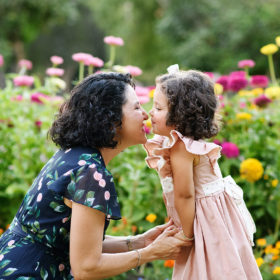 Mom does eskimo kiss to daughter in front of wildflowers at Sacramento Capitol