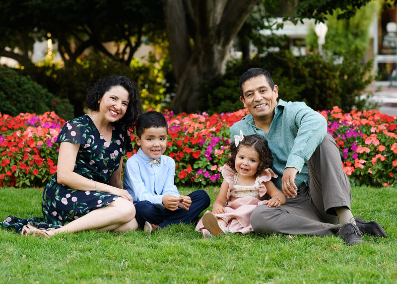 Family sits on the grass in front of colorful flowers at the Sacramento Capitol