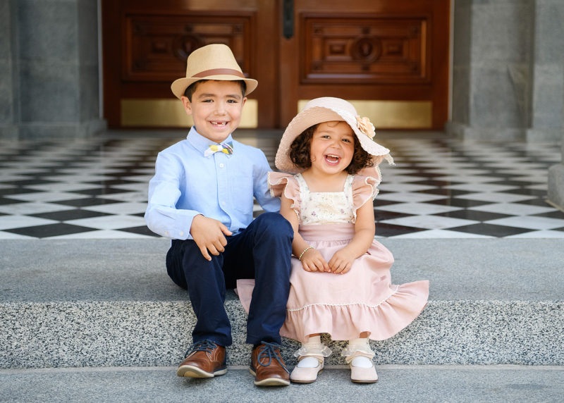 Brother and sister sitting on Sacramento Capitol steps wearing straw hats and smiling