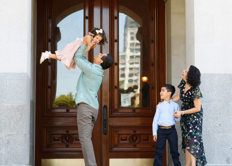 Dad lifting up daughter while mom and brother watch in front of Sacramento Capitol doors