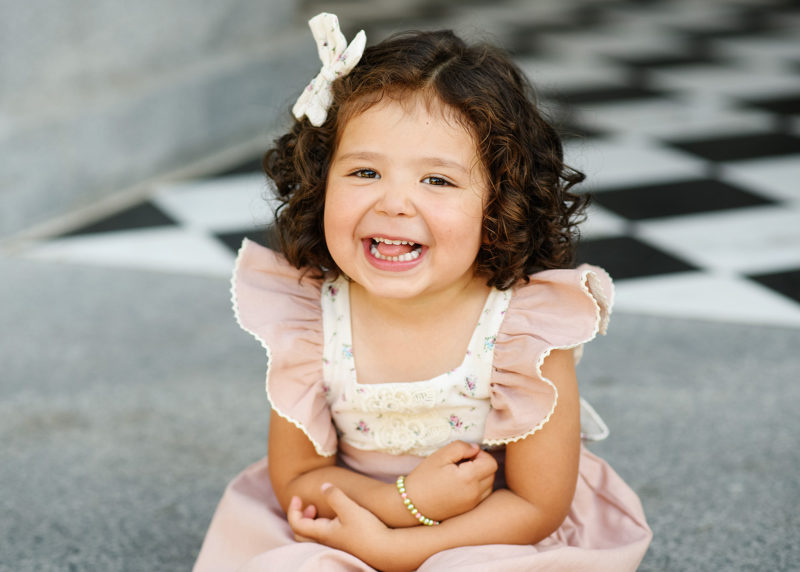 Toddler girl smiling directly at camera while sitting on Sacramento Capitol steps
