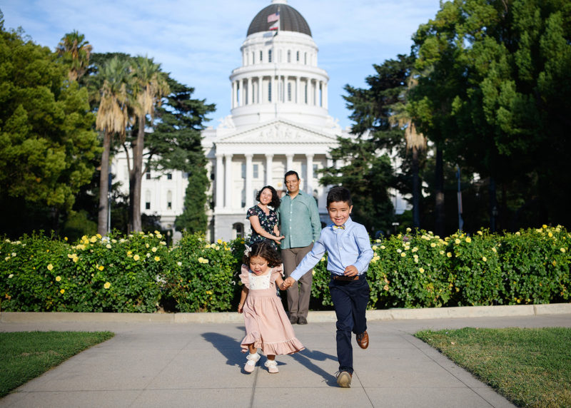 Brother and sister run hand in hand while mom and dad watch in the background in front of Sacramento Capitol building